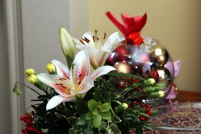 Closeup of holiday centerpiece featuring lilies and berries.